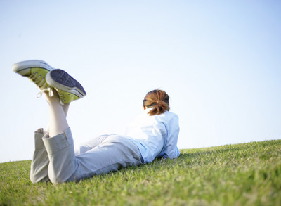 Young Woman Lying on Stomach on Grass